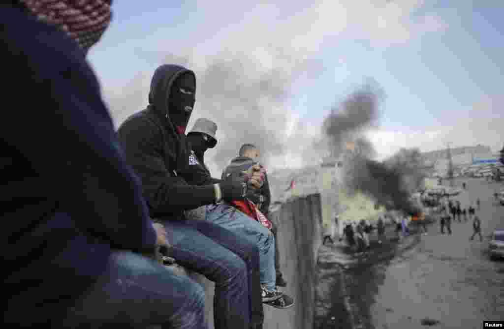 Người biểu tình Palestine ngồi trên đỉnh một phần hàng rào gây tranh cãi của Israel chia cắt thành phố Abu Dis ở Bờ Tây khỏi Jerusalem.