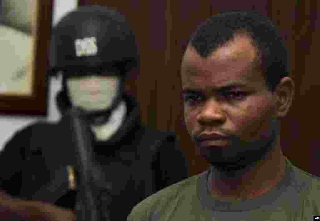 Kabiru Sokoto, a suspect in a Christmas Day bomb attack of St. Theresa Catholic Church in Madalla near Nigeria's capital, is guarded by a security official inside the state security service office in the capital Abuja February 10, 2012.
