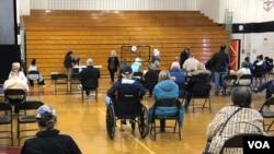 资料照片:以老人为主的民众在马里兰州蒙哥马利郡由某高中体育馆临时改建的新冠疫苗接种中心接种疫苗后坐在观察区内。(2021年3月22日)