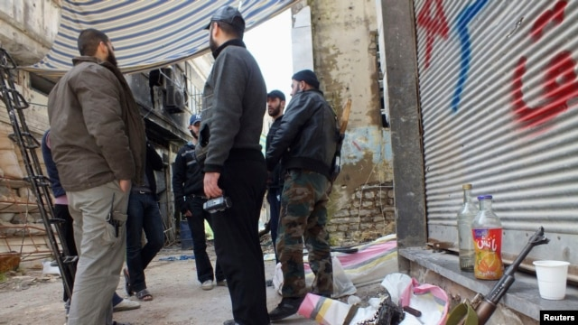 Free Syrian Army fighters stand by their weapons in a street in Homs March 9, 2013.