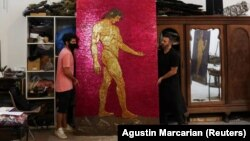 """Argentine artist Marcelo Toledo (R) and his assistant Facundo Mineldin shift an art piece depicting Adam, which will be part of the """"Museum of the After"""", at his workshop in Buenos Aires, Argentina March 4, 2021. (REUTERS/Agustin Marcarian)"""