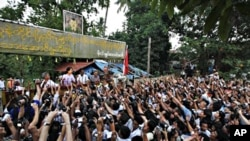 Burma's pro democracy leader Aung San Suu Kyi addresses her supporters from her house compound after her release from house arrest in Yangon, 13 Nov. 2010