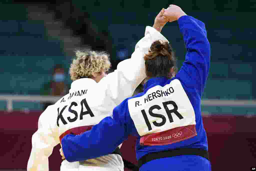 Tahani Alqahtani of Saudi Arabia, left, and Raz Hershko of Israel react after competing in their women's +78kg elimination round judo match at the 2020 Summer Olympics in Tokyo, Japan.