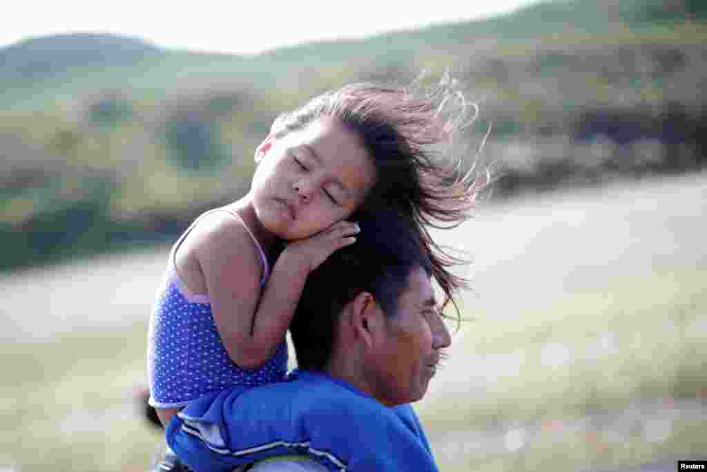 Rosendo Noviega, a 38-year-old migrant from Guatemala, part of a caravan of thousands from Central America en route to the United States, holds his daughter Belinda Izabel as he walks along the highway to Juchitan from Santiago Niltepec, Mexico, Oct. 30, 2018.