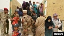 Pasukan Irak membantu warga sipil yang mengungsi dari kota Fallujah, Sabtu (18/6).