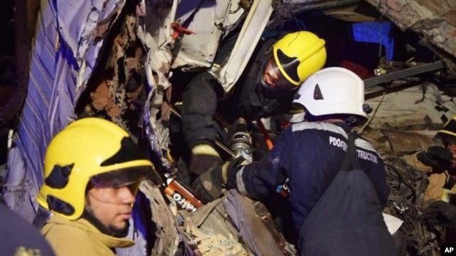 In this photo made available by the Oman Police, Omani civil defense workers rescue people from a damaged bus after a crash, near Nahdah area on the road connecting the cities of Fahud and Ibriin, in Oman, March 1, 2016.