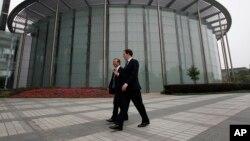 英国财政大臣乔治•奥斯本与华为公司CEO和创始人任正非在深圳参观华为总部会晤之前一道走过一座会议厅。(2013年10月16日)