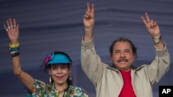 FILE - Nicaragua's President Daniel Ortega, right, and first lady Rosario Murillo, wave to supporters during an event commemorating the 36th anniversary of the Sandinista National Liberation Front withdrawal to Masaya, in Managua, Nicaragua, July 3, 2015.