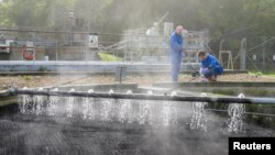 Dr Francis Hassard and Nigel Janes sample partially treated wastewater for COVID-19 as part of a study at the Cranfield University Wastewater Treatment Works in Cranfield in Cranfield, Britain in this undated photograph. (Christian Trampenau/Cranfield University via REUTERS)