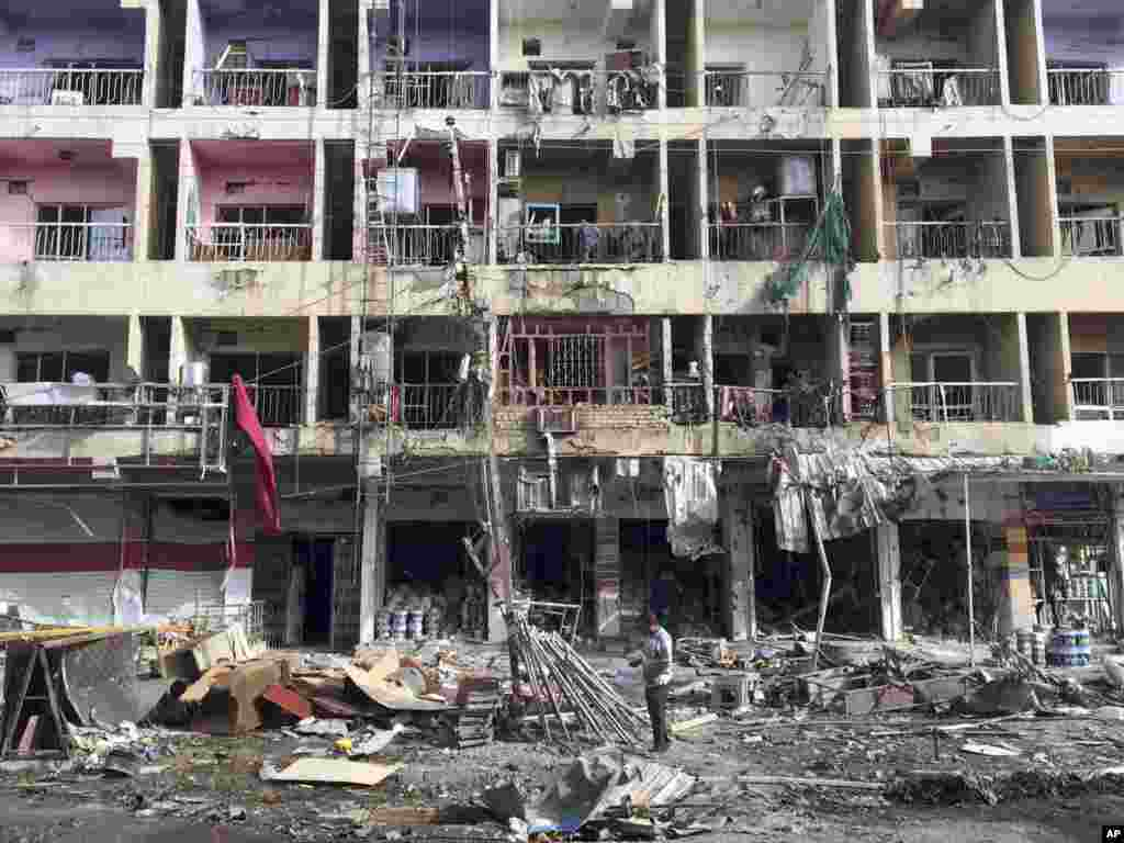 Iraqi civilians inspect the aftermath of a car bombing in the southeastern district of New Baghdad, Iraq, June 8, 2014.