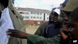 津巴布韋民眾投票站外檢視選舉結果。