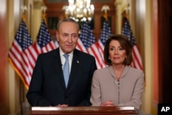 FILE - House Speaker Nancy Pelosi, right, and Senate Minority Leader Chuck Schumer pose for photographers after speaking on Capitol Hill in response President Donald Trump's prime-time address on border security, in Washington, Jan. 8, 2019.