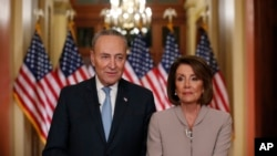 House Speaker Nancy Pelosi, right, and Senate Minority Leader Chuck Schumer pose for photographers after speaking on Capitol Hill in response President Donald Trump's prime-time address on border security, in Washington, Jan. 8, 2019.