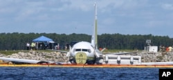 A charter plane carrying 143 people and traveling from Cuba to north Florida sits in a river at the end of a runway, May 4, 2019 in Jacksonville, Fla.