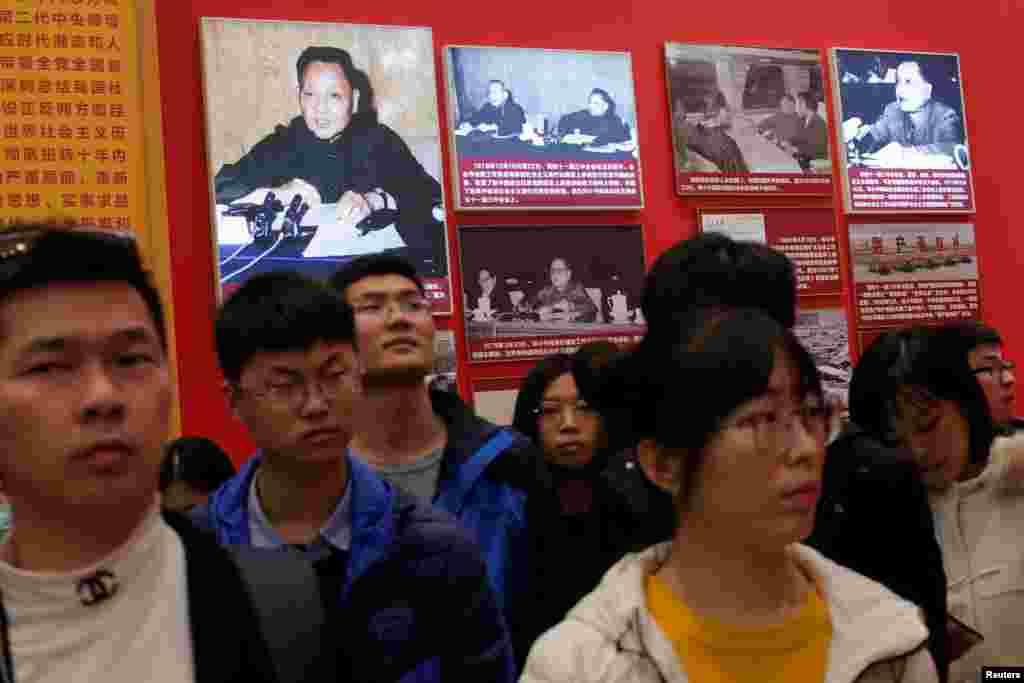 """2018年11月14日,北京中国国家博物馆举办的中国改革开放40周年展览中,人们参观关于中国前领导人邓小平的内容。其中有邓小平和陈云在中共11届三中全会上的照片,邓小平在日本乘坐高速列车的照片和1979年3月30日邓小平在理论工作务虚会议上做报告的照片。报告题为《坚持四项基本原则》,引起批毛派和自由派的不满。不过也有大学生在学习会上说:""""听邓小平的吧,没有他,我们也上不了大学。""""这次务虚会议上有不少中共党内人士批评毛泽东的言论。"""