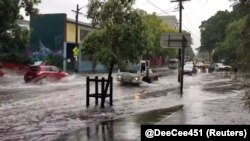 Vehicles drive on a flooded street in Sydney, New South Wales, Australia, Nov. 28, 2018 in this still image taken from a video obtained from social media.