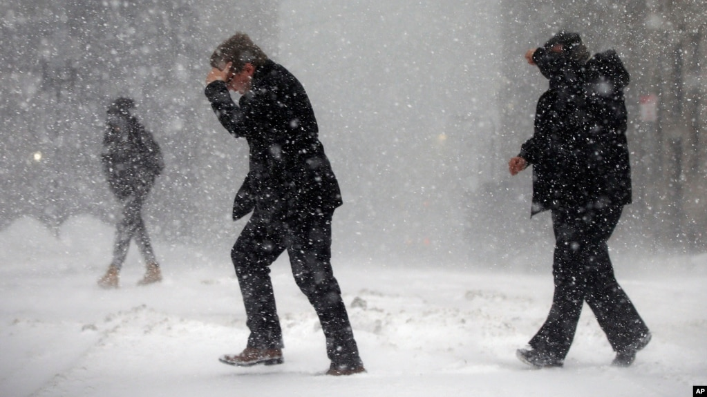 Pedestrians cross the street in downtown Boston, Jan. 4, 2018. A massive winter storm swept from the Carolinas to Maine on Thursday in the United States. (AP Photo/Michael Dwyer)