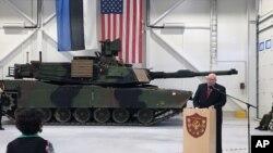 Duta Besar AS untuk Estonia James D. Melville Jr. berpidato di depan tank militer AS, dalam upacara serah terima pangkalan militer yang diperbaiki di Tapa, Estonia (15/12). (AP/Vitnija Saldava)