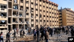 Na fotograifji zvanične sirijske novinske agencije SANA vide se Sirijci okupljeni oko mesta eksplozije na univerzitetu u Alepu, 15. januara 2013.