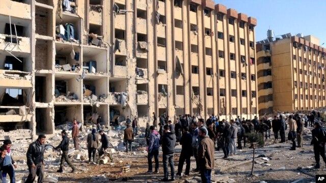 Warga Suriah berkumpul di dekat lokasi ledakan di Universitas Aleppo, Suriah, 15 Januari 2013. (AP Photo/SANA). Jumlah korban dalam ledakan ini dilaporkan mencapai 83 orang tewas dan lebih dari 150 orang lainnya luka-luka.