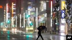 Un hombre cruza una calle en el distrito comercial Ginza bajo la lluvia provocada por el tifón Hagibis en Tokio, el sábado 12 de octubre de 2019.