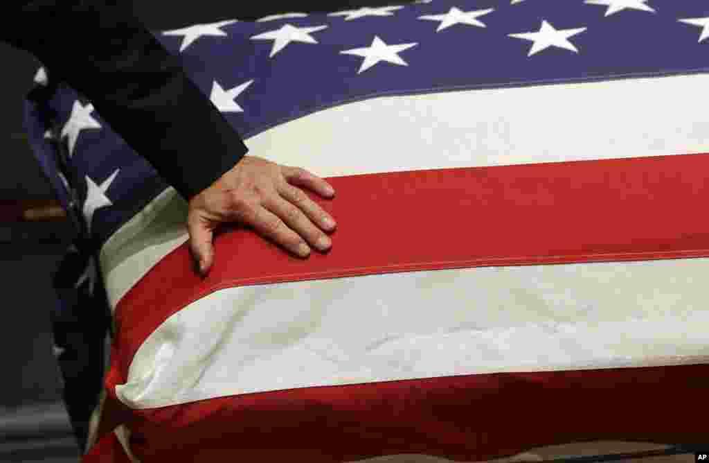 Wakil Presiden Joe Biden meletakkan tangannya di peti mati anaknya, mantan Jaksa Agung Delaware Beau Biden, di Legislative Hall di Dover, Delaware, 4 Juni 2015.