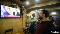 Seorang warga Palestina menonton konferensi pers gabungan Presiden AS Donald Trump dan Perdana Menteri Israel Benjamin Netanyahu, dari sebuah kafe di Hebron, Tepi Barat (15/2). (Reuters/Mussa Qawasma)