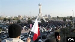 Warga Bahrain mengibarkan bendera dan mengambil foto para demonstran di ibukota, Manama, Selasa (2/15).