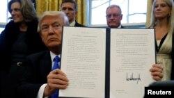 Tổng thống Donald Trump giơ một sắc lệnh hành pháp mà ông vừa ký trong Phòng Bầu dục tại Tòa Bạch Ốc ở Washignton, ngày 28 tháng 1, 2016.