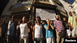 Members of 'Stop Desahucios' [Stop evictions], 15M and 'Afectados X la Hipoteca' [Mortgage Victims Platform] block the door of the building of the Lopez family's flat, before being evicted for failing to pay their mortgage, in Malaga, July 6, 2012.