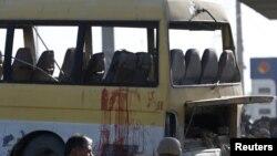 Petugas keamanan Afghanistan memeriksa bercak-bercak darah pada minibus yang terkena bom bunuh diri di Kabul, Afghanistan (20/8).