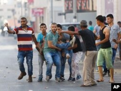 Palestinians carry an injured man during an Israeli military raid in the West Bank city of Jenin, Oct. 4, 2015.