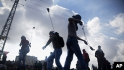 FILE - Palestinian protesters use slingshots to throw stones towards Israeli security forces during clashes following a protest marking the 11th anniversary of the death of late Palestinian leader Yasser Arafat, in the West Bank city of Ramallah, Wednesda