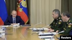 지난해 5월 블라디미르 푸틴 러시아 대통령(왼쪽)이 세르게이 쇼이구 러시아 국방장관(가운데)과 국방부 고위 관리들과 소치 시에서 만나 회의를 주재하고 있다. (자료사진)