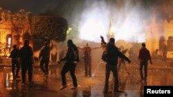 Para demonstran anti-pemerintah melemparkan batu dan bom molotov ke arah petugas keamanan yang berjaga di depan Istana Keperesidenan Mesir (1/2).