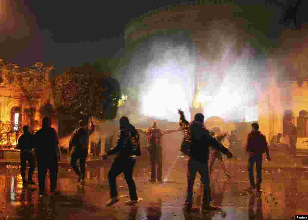 Protesters throw stones at security forces inside the presidential palace during clashes in front of the palace in Cairo, Feb. 1, 2013.
