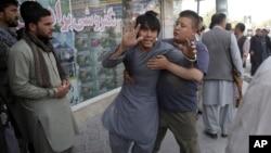 مردی که براثر حمله روز جمعه شوکه شده و توسط همراهانش برده می شود.