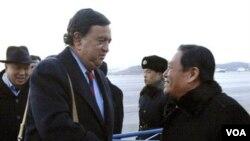 Bill Richardson (kiri) disambut oleh pejabat Kementerian Luar Negeri Korut, Li Gun di bandara Pyongyang, Korea Utara, Minggu, 19 Desember.