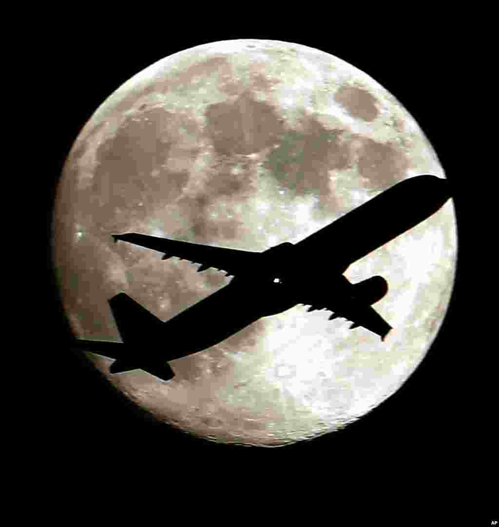 A airlines jet plane approaching Los Angeles International Airport crosses the moon as seen from Palm Park in Whittier, California, USA, Aug. 19, 2013.