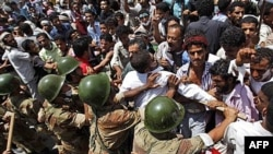 Binh sĩ Yemen đẩy người biểu tình chống chính phủ trong một cuộc biểu tình tại Taiz đòi Tổng thống Ali Abdullah Saleh từ chức, ngày 9 tháng 4, 2011
