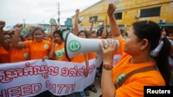 Garment workers shout during a protest calling for higher wages in Phnom Penh, Sept. 17, 2014.