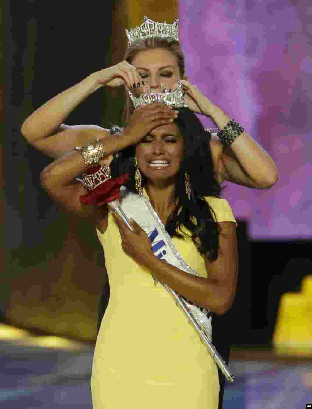 Miss New York Nina Davuluri is crowned as Miss America 2014 by Miss America 2013 Mallory Hagan in Atlantic City, N.J., Sept. 15, 2013.