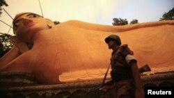 Một thành viên của Bộ đội biên phòng Bangladesh (BGB) bảo vệ một tác phẩm điêu khắc của Phật giáo tại làng Cox's Bazaar, ngày 1/10/2012
