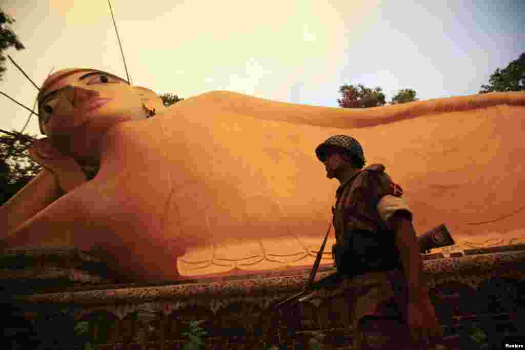 A member of the Border Guard Bangladesh (BGB) guards a Buddha sculpture after an attack by Muslims in Cox's Bazar, Bangladesh, October 1, 2012.