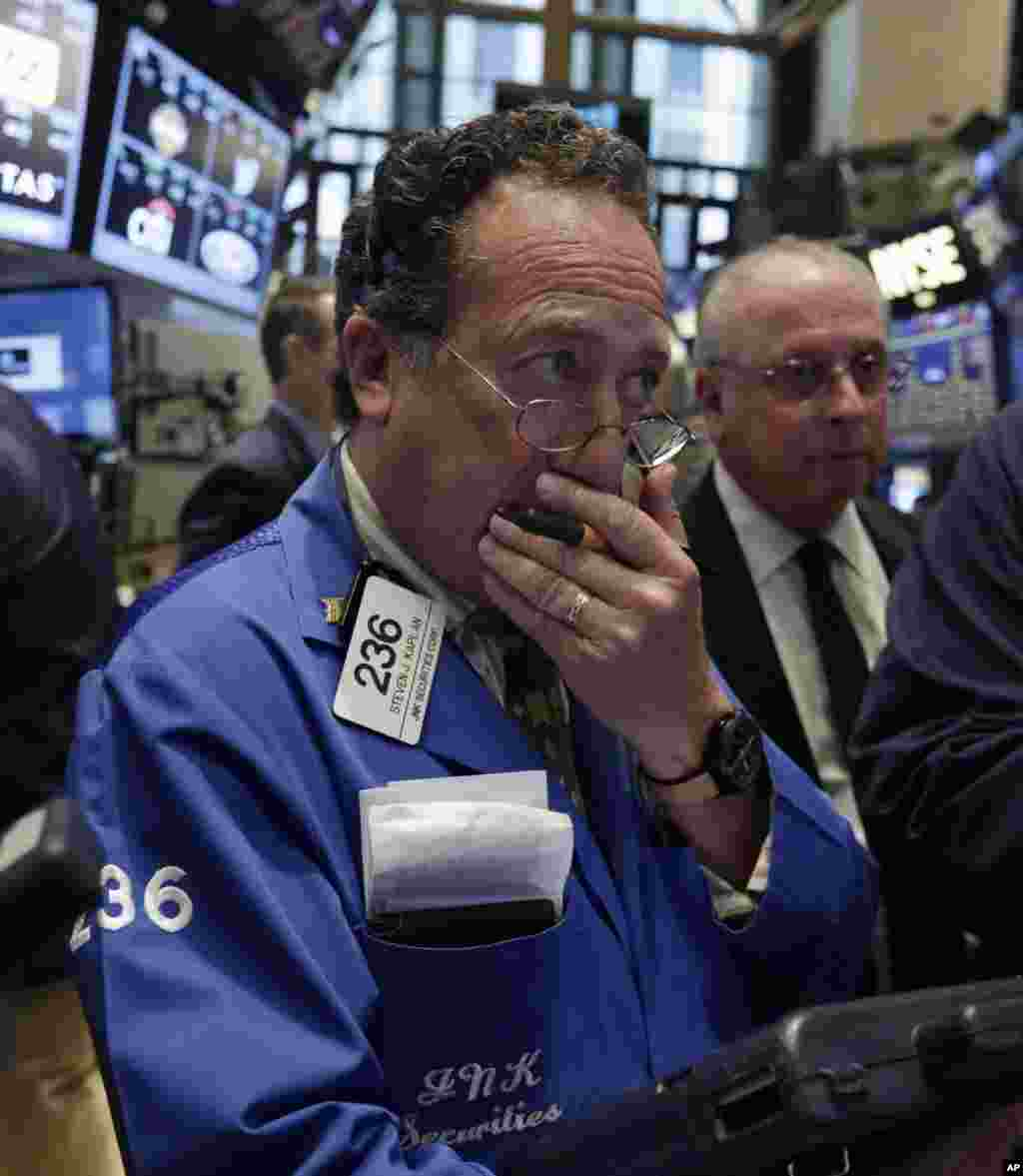 Worries about Russian troops amassing near the Ukrainian border are pushing stocks slightly lower. Trader Steven Kaplan, left, works on the floor of the New York Stock Exchange, New York, NY, Aug. 6, 2014.