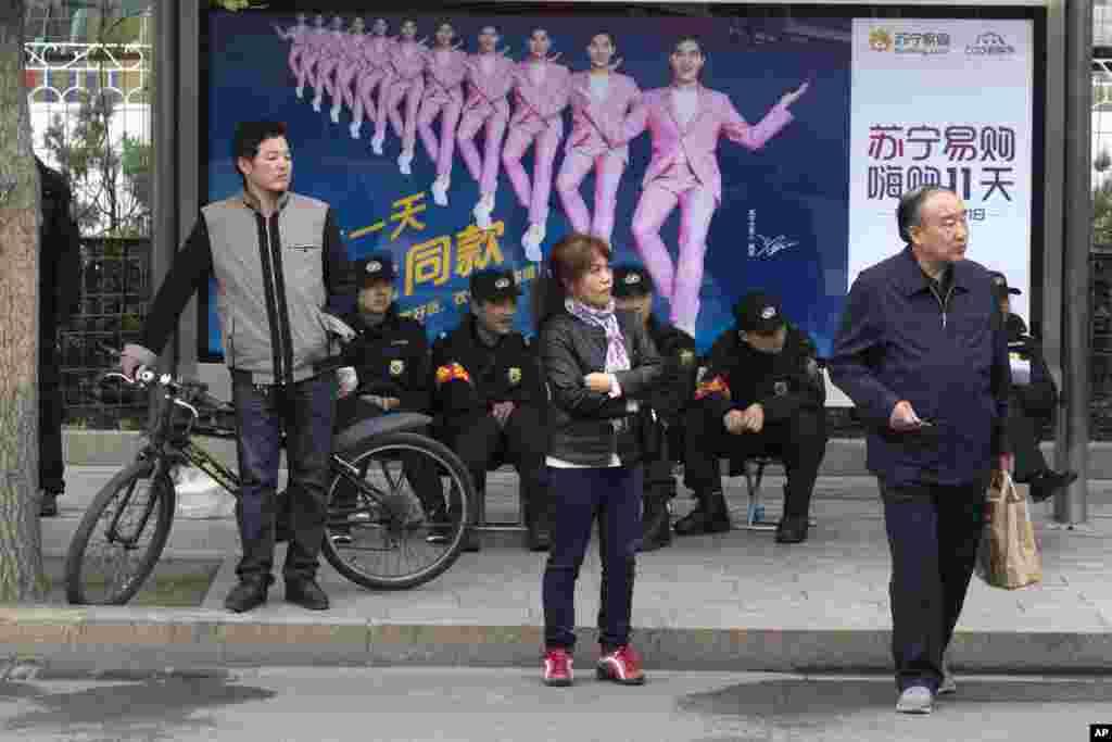 """十九大期间北京街头坐着的的5名佩戴红袖章的安保人员,左侧还站着一个(2017年10月21日)。 这是北京高密度安保的缩影。大会期间北京安保措施空前,包括关闭夜店酒吧,禁止燃放鞭炮,实行交通管制,出动军人军车。据说还出动了被网民戏称为北京五大神秘组织的""""朝阳群众""""、""""西城大妈""""、""""海淀网友""""、""""丰台劝导队""""以及以学生为主的""""网警志愿者""""。"""