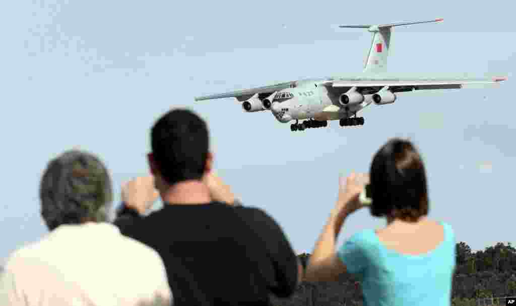 Spectators take photos of a Chinese Ilyushin IL-76 aircraft as it comes in for a landing at Perth International Airport after returning from the ongoing search operations for missing Malaysia Airlines Flight 370, Perth, Australia, April 10, 2014.