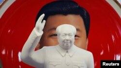 北京天安门附近一个纪念品商店里毛泽东的塑像摆在习近平纪念画盘的前面。(2018年3月1日)