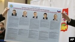 Russian election officials hold an election poster with portraits of the presidential candidates, Feb. 7, 2012.