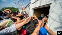 15일 세르비아와 헝가리 국경 지역에서 난민들이 구호 식품을 배급받고 있다.